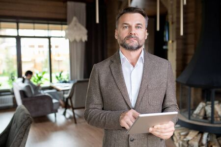 Serious middle aged businessman with beard scrolling in touchpad in restaurant