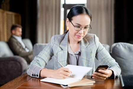 Young elegant businesswoman scrolling in smartphone while making working notes