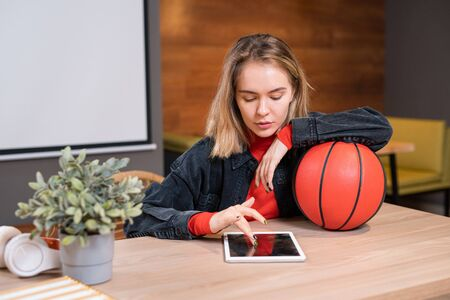 Young blonde woman in casualwear sitting in cafe and scrolling in touchpad Reklamní fotografie