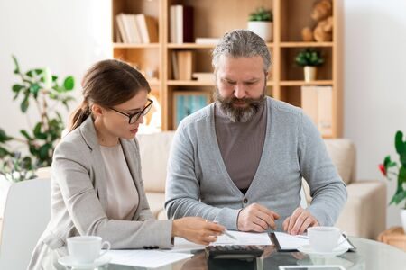 Young confident insurance agent explaining retired man points of the contract Stock Photo