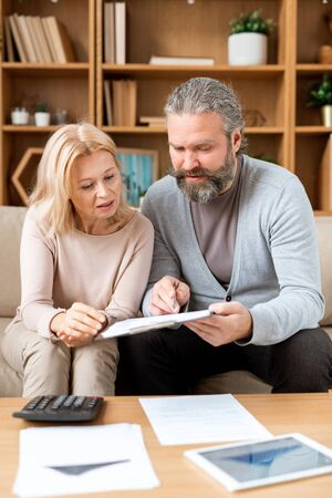 Mature woman listening to her husband pointing at document while reading it Stock Photo