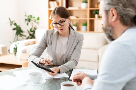 Young accountant with calculator pressing buttons and consulting with colleague