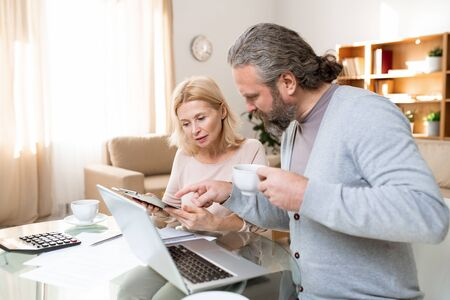 Mature bearded man with cup of tea pointing at document held by his wife Stock Photo