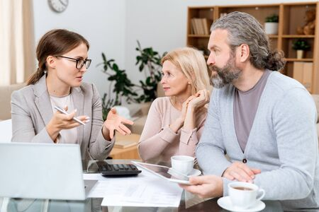 Mature couple and real estate agent discussing financial points Stock Photo