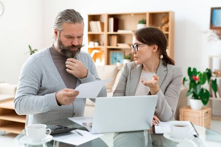Pensive bearded man looking through paper while listening to real estate agent Stock Photo
