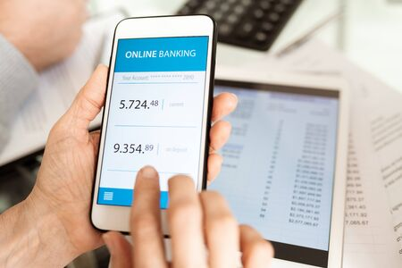 Hands of businessperson with smartphone scrolling through online banking account