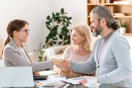 Happy young real estate agent congratulating mature clients on successful deal Stock Photo