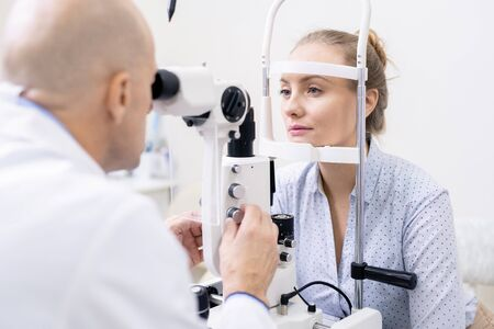 Young female looking at ophthalmologist while having her eyesight examined