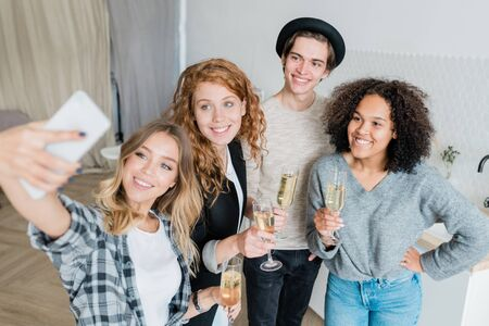 Group of happy young multicultural friends with champagne making selfie at party
