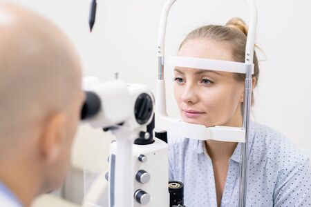Young woman having her eyesight checked by special optometric equipment