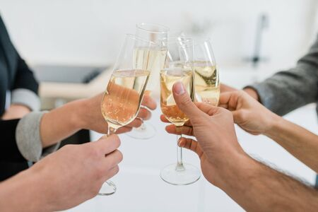 Hands of friends holding flutes of sparkling of champagne and clinking with them
