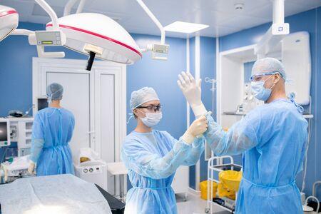 Junge Assistentin, die dem Chirurgen Gummihandschuhe anzieht, während sie sich auf die Operation im Krankenhaus vorbereitet