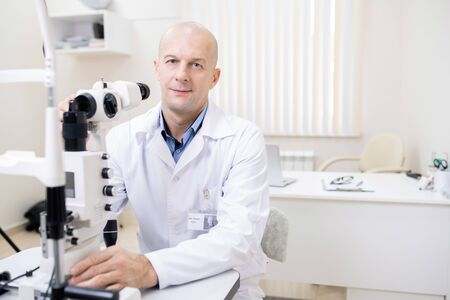 Successful professional optometrist working with new eyesight check-up equipment 스톡 콘텐츠