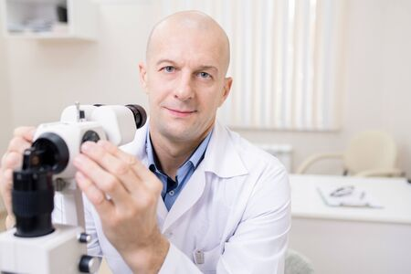 Bald middle aged eye doctor sitting in front of camera by workplace 스톡 콘텐츠
