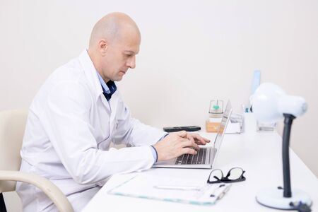 Serious middle aged doctor in whitecoat concentrating on laptop work