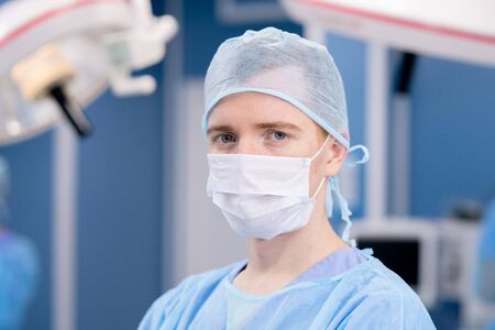 Young intern or surgeon in protective mask and uniform looking at you