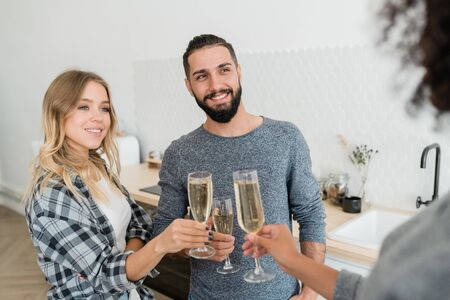 Happy young casual couple with flutes of champagne toasting with mixed-race girl