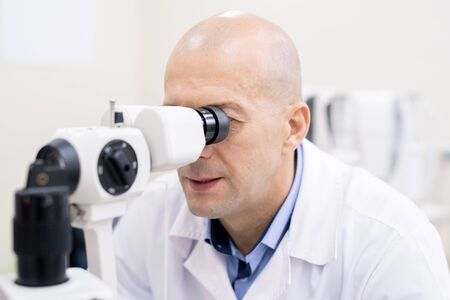 Professional ophthalmologist looking through medical equiment by workplace while checking eyesight of patient at work