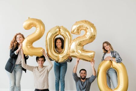 Happy teenagers standing along white wall while holding number of next year