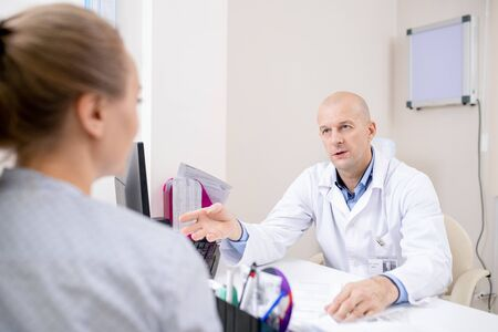 Confident doctor in whitecoat sitting by workplace while consulting patient