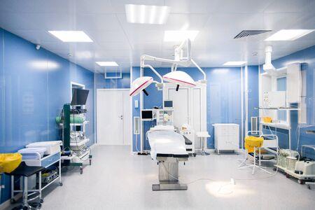 Interior de la sala de operaciones en clínicas modernas con todo el equipo necesario a lo largo de las paredes y mesa quirúrgica en el centro con lámparas arriba