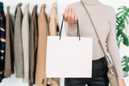 Young stylish female shopper with handbag standing in front of camera while spending time and money in boutique