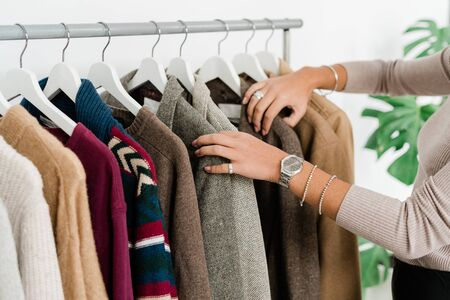 Casual young female shopaholic standing by row of new stylish clothes while choosing jacket or sweater
