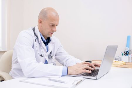 Bald male professional in whitecoat concentrating on work in front of laptop
