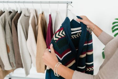 Young woman holding hanger with new warm knitted cardigan while choosing clothes from seasonal collection