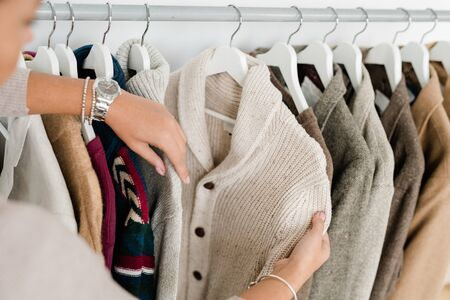 Hands of young woman holding white knitted cardigan while choosing new clothes in modern boutique Imagens