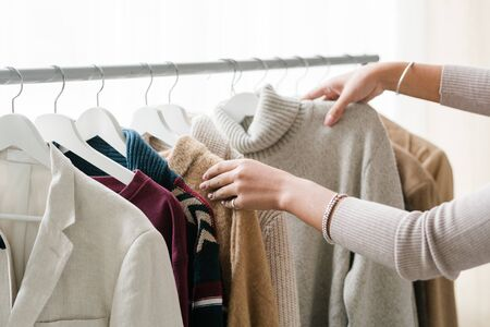 Hands of young female shopper choosing warm knitted and woolen clothes from new seasonal casualwear collection