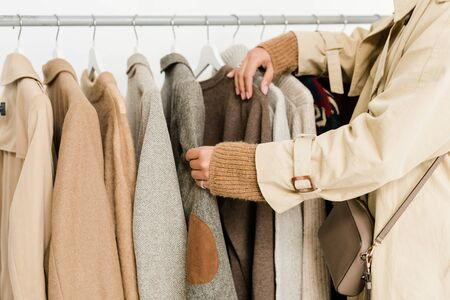 Contemporary young woman in beige trenchcoat and knitted pullover choosing casualwear from new seasonal collection in boutique