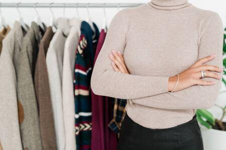Mid-section of young elegant woman in casualwear crossing her arms on chest while standing in casualwear boutique
