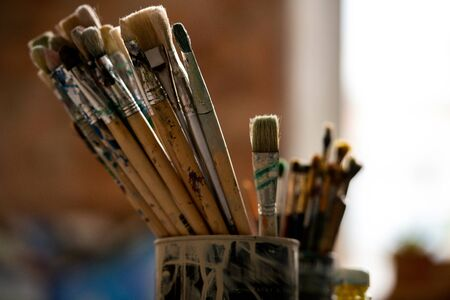 Set of paintbrushes for professional painting in tin can inside modern studio