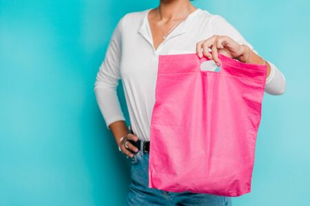 Mid-section of casual young female in white polo shirt and blue jeans holding fucsia pink shopping bag in isolation Stock Photo