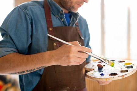 Modern painter in apron holding palette with mixed colors and paintbrush