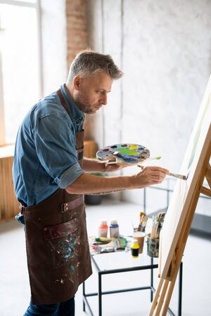 Contemporary painter with palette and paintbrush working over painting