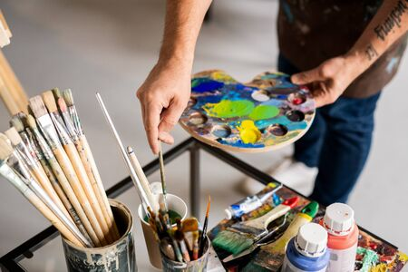 Painter holding palette with mixed colors and putting paintbrush in water Banco de Imagens