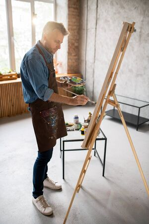 Casual man in apron standing in front of easel and painting with water colors Banco de Imagens