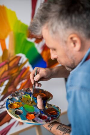 Contemporary professional painter mixing gouache or oil color on palette