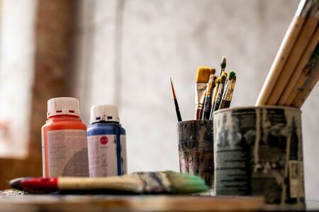 Set of paintbrushes in tin cans and two plastic jars with red and blue gouache Banco de Imagens