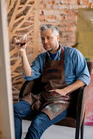 Pensive artist with glass of red wine looking at his painting on easel Stock Photo