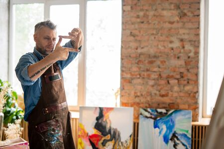 Professional painter looking at easel through frame made up of fingers Banco de Imagens