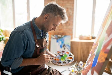 Creative man in apron mixing colors on palette in front of easel in studio 版權商用圖片
