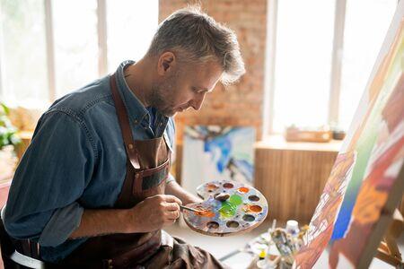Kreativer Mann in Schürze, der Farben auf Palette vor Staffelei im Studio mischt Standard-Bild