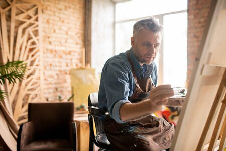 Professional painter in workwear sitting in front of unfinished painting Stock fotó