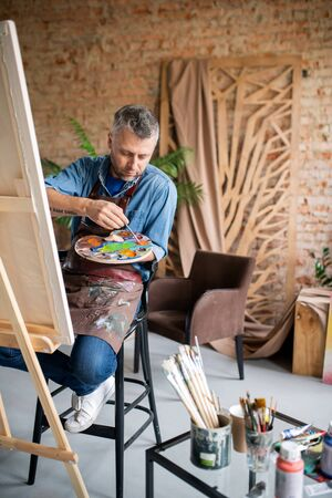 Contemporary painter in casualwear and apron mixing colors on palette