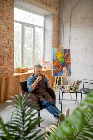 Restful painter in workwear having cup of tea or coffee at break in studio