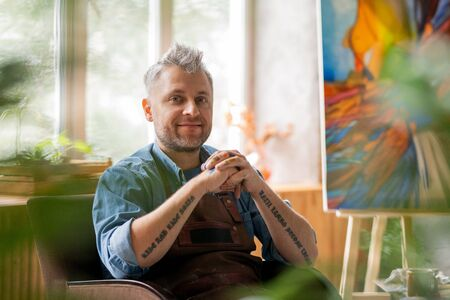 Happy creative painter in workwear looking at you while having rest in armchair