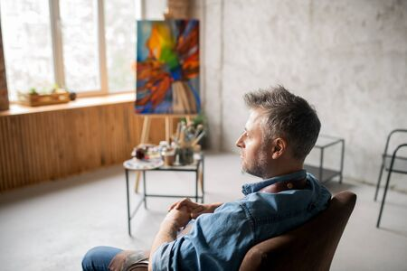 Middle aged pensive and restful painter in workwear sitting in armchair